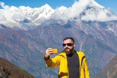 Équipez prendre l'autoportrait avec le téléphone pendant le trekking de montagne photo stock