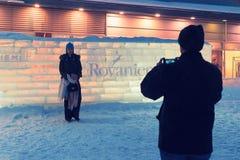 Équipez prendre la photo de la femme au mur Iced dans Rovaniemi image stock