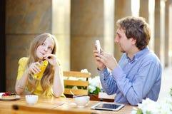 Équipez prendre la photo de la jeune femme à l'aide de son téléphone intelligent images stock