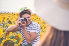 Équipez prendre la photo de son amie dans le domaine de tournesol Image stock