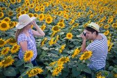 Équipez prendre la photo de son amie dans le domaine de tournesol Images libres de droits