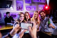 Équipez prendre la photographie de ses amis avec le téléphone portable Image stock