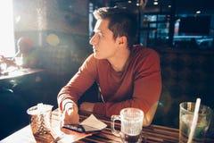Équipez prendre le petit déjeuner de matin avec du café en café de wagon-restaurant et à l'aide de son téléphone portable photographie stock