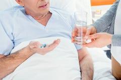 Équipez prendre les médecines et la femme tenant le verre de l'eau Photo stock