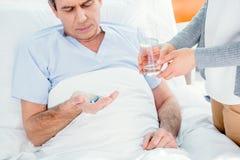 Équipez prendre les médecines et la femme tenant le verre de l'eau Images libres de droits