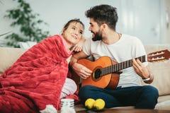 Équipez prendre soin de son amie malade se trouvant sur le sofa Photo stock