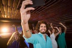 Équipez prendre un selfie de téléphone portable tandis que des amis dansant sur la piste de danse Photos stock