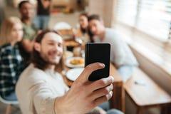 Équipez prendre une photo de selfie avec des amis dans la cuisine Photographie stock libre de droits
