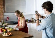Équipez prendre une photo de son épouse dans la cuisine Images libres de droits
