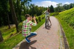 Équipez prendre une photo de son girfriend se reposant sur un vélo Images stock