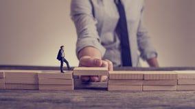 Équipez résoudre des problèmes en construisant le pont avec le bloc en bois Photos stock