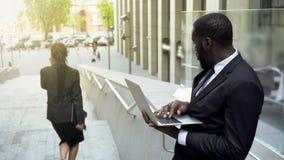 Équipez regarder affectueusement la dame attirante d'affaires passant par, distrait image libre de droits