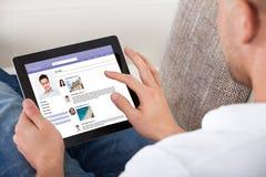 Équipez regarder des profils personnels sur un comprimé Photos libres de droits