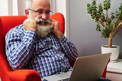 Équipez regarder l'ordinateur portable et déchirer sa barbe Photo libre de droits