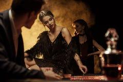 Équipez regarder la femme s'asseyant sur la table de tisonnier dans le casino photos libres de droits