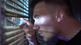 Équipez regarder la fenêtre par les aveugles à la rue, remarquant banque de vidéos