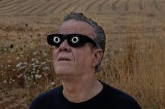 Équipez regarder la pleine éclipse solaire avec l'éclipse se reflétant dans des lentilles Photographie stock libre de droits