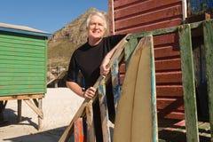 Équipez regarder parti tout en se tenant la hutte de plage Photos stock