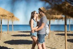 Équipez regarder son amie touchant son visage sur la plage Image stock
