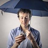 Équipez regarder son téléphone portable avec un parapluie Photos stock