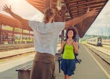 Équipez rencontrer son amie à la station de train Photographie stock libre de droits