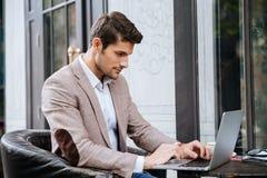 Équipez reposer et à l'aide de l'ordinateur portable en café extérieur Photos libres de droits