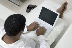 Équipez reposer sur le sofa utilisant la vue courbe d'ordinateur portable photos stock