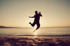 Équipez sautent dans le coucher du soleil sur la plage Image stock