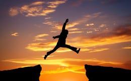 Équipez sautent par l'espace sur le fond ardent de coucher du soleil Photo libre de droits