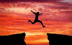 Équipez sauter à travers l'espace d'une roche à s'accrocher à l'autre image libre de droits