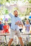 Équipez sauter avec un gâteau sur une célébration de famille ou une réception en plein air dehors photo stock