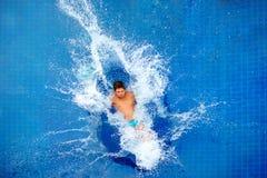 Équipez sauter dans la piscine, éclaboussure énorme, vue supérieure photographie stock