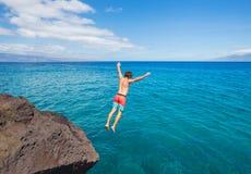 Équipez sauter outre de la falaise dans l'océan image stock