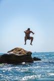 Équipez sauter outre de la falaise dans la mer image libre de droits