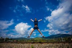 Équipez sauter pour la joie sur une colline d'herbe au-dessus de ligne d'horizon Photos libres de droits