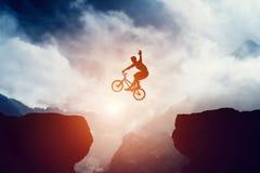 Équipez sauter sur le vélo de bmx au-dessus du précipice en montagnes au coucher du soleil Photo libre de droits