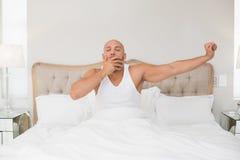 Équipez se réveiller dans le lit et étirer ses bras Photo libre de droits