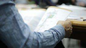 Équipez se reposer à la conférence poussant des feuilles par une magazine avec des diagrammes et des dessins banque de vidéos