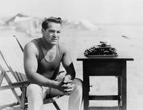 Équipez se reposer à la plage avec sa machine à écrire (toutes les personnes représentées ne sont pas plus long vivantes et aucun photographie stock libre de droits