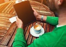 Équipez se reposer à la table avec la tasse de café tout en à l'aide du comprimé d'écran tactile avec l'écran vide Images libres de droits