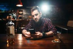 Équipez se reposer au compteur de barre et à l'aide de son téléphone images stock