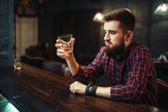 Équipez se reposer au compteur de barre et buvez l'alcool photographie stock