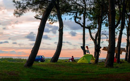 Équipez se reposer au coucher du soleil sur la plage près des tentes sous des arbres Image stock