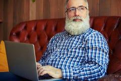 Équipez se reposer avec l'ordinateur portable et regarder la fenêtre Photographie stock libre de droits