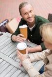 Équipez se reposer avec son amie tout en buvant du café jetable au café Image libre de droits