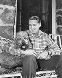 Équipez se reposer avec son chien sur les meubles en osier (toutes les personnes représentées ne sont pas plus long vivantes et a Photographie stock