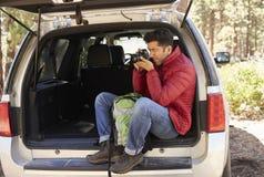 Équipez se reposer dans le dos nu de la voiture prenant des photos dans la forêt Images libres de droits
