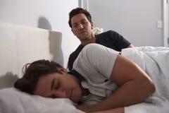 Équipez se reposer dans le lit, regardant tandis que son ami dort Photos libres de droits
