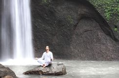 Équipez se reposer dans le yoga de méditation sur la roche à la cascade Tibumana Image stock