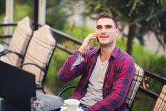 Équipez se reposer dans un café sur une pause-café Utilisant le téléphone images stock